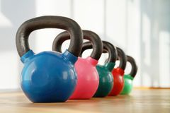 Colorful kettlebells in gym. Colorful kettlebells in a row in a gym Stock Photography