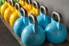 Colorful kettlebells in a row in a gym - focus on the front kett Royalty Free Stock Image