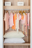 Colorful kid's clothes hanging on bar in wooden wardrobe Royalty Free Stock Photos