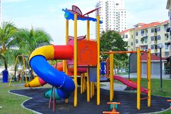 Children playground near the houses. Colorful kid`s playground which consists of slides, swings, and others for kid`s enjoyment and play Royalty Free Stock Image