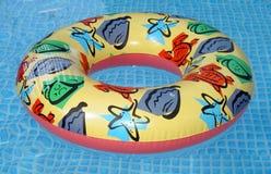 Colorful Kiddie Life Saver. Colorful kiddie life preserver saver in blue pool Royalty Free Stock Images