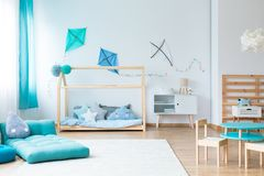 Colorful kids bedroom with kites. Drop shaped pillow on blue mattress on white carpet in colorful kids bedroom with blue kites on wall royalty free stock photos