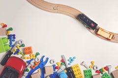 Colorful kids toys: plastic toy tools, bolts, nuts, car, train with wooden rail on white background as frame. Top view. Royalty Free Stock Images