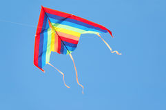 Colorful kite. A colorful triangle, textile kite flying over blue sky Stock Photography