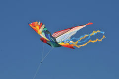 Colorful kite. A very colorful bird shaped kite is flown in a clear blue sky Stock Photo