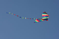 Colorful kite in the air. Flying a colorful kite in the blue sky Stock Photos