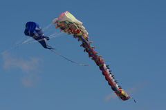 Colorful kite in the air. Flying a colorful kite in the blue sky Royalty Free Stock Photography
