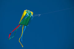 Colorful kite in blue sky. A colorful box kite flying in a cloudless, blue sky royalty free stock photo
