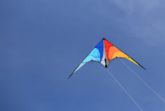 Colorful kite in blue sky. Kite on summer sky background close-up Stock Photos