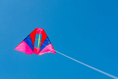 Colorful kite flying against blue sky background Royalty Free Stock Image