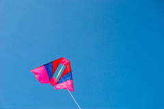 Colorful kite flying against blue sky background Stock Photography