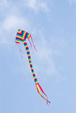 Colorful kite flying in blue sky. Stock Image
