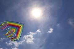 Colorful kite flying in blue sky background sky. Bright sun.  royalty free stock photography