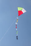 Colorful kite flying in a blue sky Stock Photography