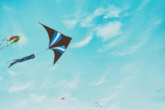 Colorful kite flying in the blue sky through the clouds.  Stock Images