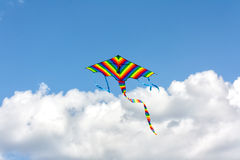 Colorful kite flying in a blue sky with clouds Stock Photography