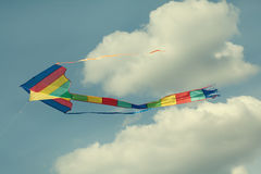 Colorful kite flying in the cloudy sky. Green yellow red blue colors model. Summer holidays concept Royalty Free Stock Images