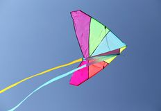 Colorful kite flying high in the sky blue Stock Photos
