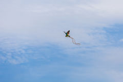 Colorful kite flying high in the sky like bird. Summer fun Stock Photography