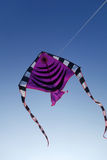 Colorful kite flying up in blue sky Royalty Free Stock Photos