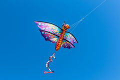 A colorful kite flying in the wind on a clear sunny day. Stock Photography