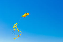 Colorful kite with tail in blue sky Royalty Free Stock Images