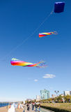 Colorful kites flying against a blue sky on the city embankment Stock Photos