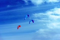 Colorful kites flying in a blue sky with air clouds. royalty free stock image