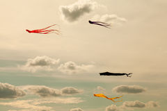 Colorful kites flying in the cloudy sky. Retro style colors Royalty Free Stock Photos