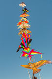 Colorful kites hanging against a blue sky Royalty Free Stock Photo