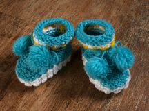 Colorful knitted baby booties on a wooden board. Royalty Free Stock Photos