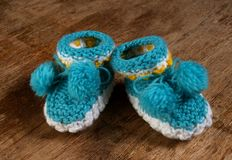 Colorful knitted baby booties on a wooden board. Stock Images