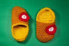 Colourful knitted Slippers on a green background royalty free stock image