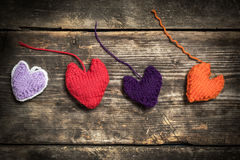 Colorful knitted hearts on the dark old boards. Valentine`s Day. Colorful knitted hearts. Red heart on the dark old boards. Valentines day. Heart pendant. Red Royalty Free Stock Photos