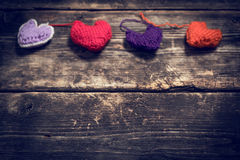Colorful knitted hearts on the dark old boards. Valentine`s Day. Colorful knitted hearts. Red heart on the dark old boards. Valentines day. Heart pendant. Red Stock Photos