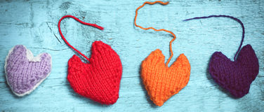 Colorful knitted hearts on the light blue boards. Valentine`s Day. Colorful knitted hearts. Red heart on the light blue boards. Valentines day. Heart pendant Stock Photography