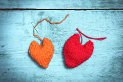 Colorful knitted hearts on the light blue boards. Valentine`s Day. Colorful knitted hearts. Red heart on the light blue boards. Valentines day. Heart pendant Stock Photos