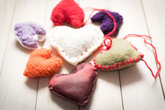 Colorful knitted hearts on light, wooden boards. Valentine`s Day. Colorful knitted hearts. Valentines day. Heart pendant. Red heart. Handmade Hearts. Valentine Stock Photography