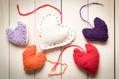 Colorful knitted hearts on light, wooden boards. Valentine`s Day. Colorful knitted hearts. Valentines day. Heart pendant. Red heart. Handmade Hearts. Valentine Royalty Free Stock Photo