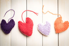 Colorful knitted hearts on light, wooden boards. Valentine`s Day. Colorful knitted hearts. Valentines day. Heart pendant. Red heart. Handmade Hearts. Valentine Stock Photos