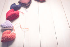 Colorful knitted hearts on light, wooden boards. Valentine`s Day. Colorful knitted hearts. Valentines day. Heart pendant. Red heart. Handmade Hearts. Valentine Royalty Free Stock Image