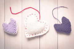 Colorful knitted hearts on light, wooden boards. Valentine`s Day. Colorful knitted hearts. Valentines day. Heart pendant. Red heart. Handmade Hearts. Valentine Stock Images