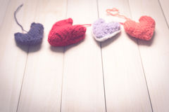 Colorful knitted hearts on light, wooden boards. Valentine`s Day. Colorful knitted hearts. Valentines day. Heart pendant. Red heart. Handmade Hearts. Valentine Royalty Free Stock Images