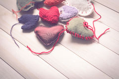 Colorful knitted hearts on light, wooden boards. Valentine`s Day. Colorful knitted hearts. Valentines day. Heart pendant. Red heart. Handmade Hearts. Valentine Royalty Free Stock Photos