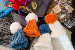 Colorful knitted miniature bonnets under the Christmas tree Royalty Free Stock Images