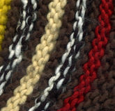 Colorful knitted sweater texture. Colorful texture of a knitted sweater with long creamy, white and black, red, yellow and brown stripes Royalty Free Stock Image