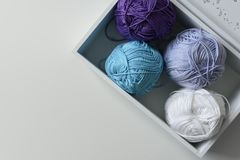 View from above on purple, blue and white knitting yarn wools in wooden box with a copy space on white table. stock photo