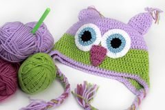 Colorful knitting owl hat, skein, hook. Colorful knitting owl hat, skeins, hook on white background Stock Images