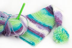 Colorful knitting striped hat, skein, hook. On white background Stock Images