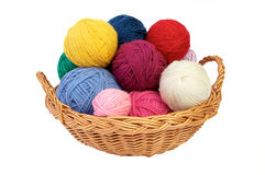 Colorful knitting yarn in a basket. Colorful yarn balls in a straw basket isolated on white background Stock Images